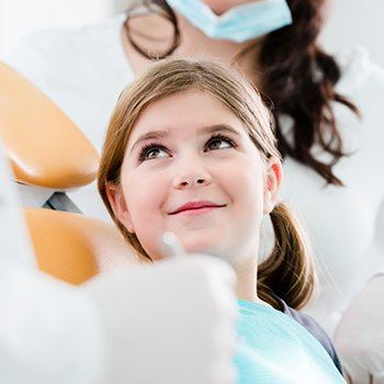 Smiling young girl in dental exam chair