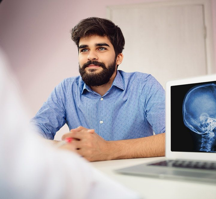Man sitting in consultation room with x-rays on computer
