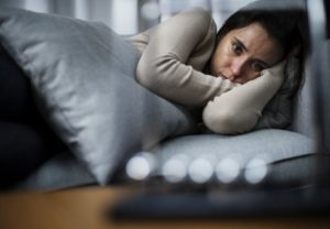 depressed young woman with sleep apnea, lying in bed