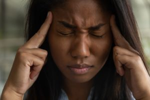 Close-up of suffering woman with migraines and TMJ dysfunction