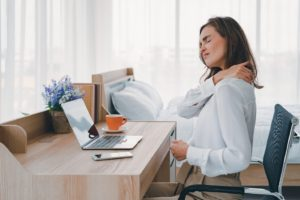 Woman sitting at computer, struggling with neck pain