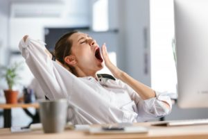 young woman yawning while working